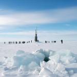 submarine poking through ice and people disembarking