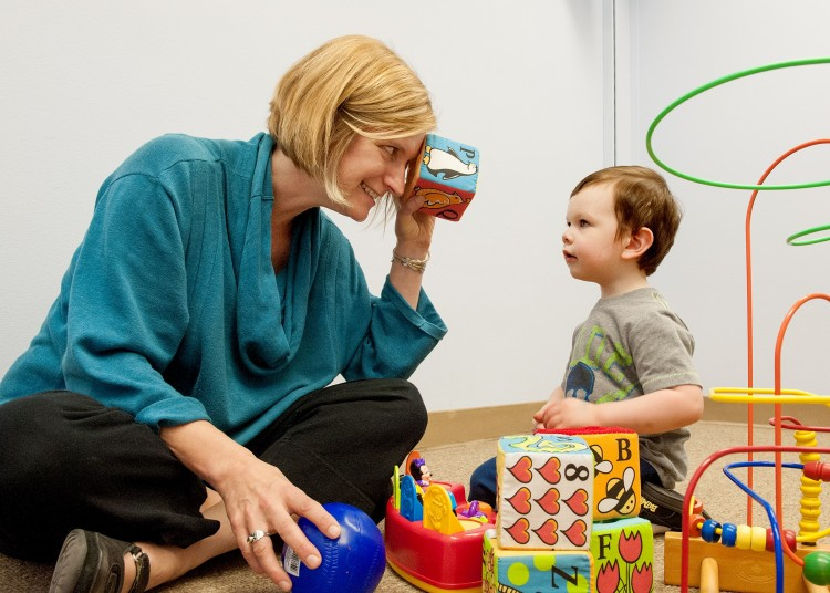 Annette Estes, left, plays with 2-year-old Caellum Ortiz at the UW Autism Center.
