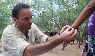 UW biologist Horacio de la Iglesia puts an activity logger onto a participant's wrist.