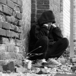 Black and white photo of boy sitting alone outside a brick building.