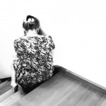 Black and white photo of woman sitting alone on stairs