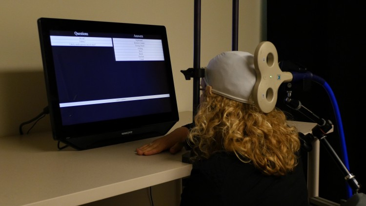 University of Washington postdoctoral student Caitlin Hudac wears a cap that uses transcranial magnetic stimulation (TMG) to deliver brain signals from the other participant.