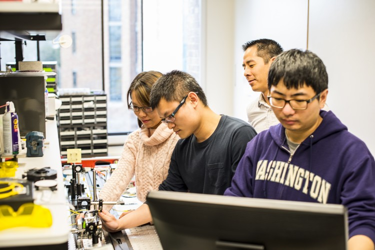 "UW mechanical engineering doctoral students and assistant professor Jonathan T.C. Liu work to align a handheld microscope for cancer detection in patients. From left to right: Ye Chen, Linpeng ""Peter"" Wei, Liu and Chengbo Yin."
