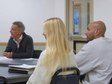 Professor Steve Herbert, left, addresses the class while UW student Alexa Cathcart and University Behind Bars student Devon Adams look on.