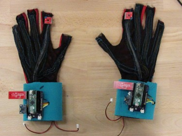 "These ""SignAloud"" gloves developed by UW students contain sensors that record hand position and movement and transmit data wirelessly to a central computer, which uses algorithms to recognize and translate sign language gestures."