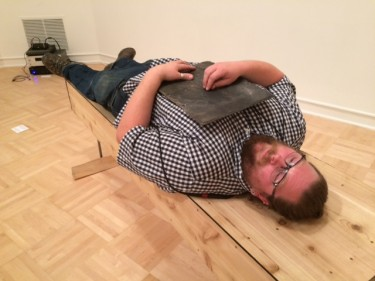"Artist Benjamin Gale-Schreck lies on his ""coffin-cradle."" He invites people to lie down on it and experience the sounds and vibrations he creates. A lot of his work relates to experiences with family, he said, back in El Paso, Illinois, where his late father started an arts center. This is at the annual MFA/M-DEsign show at the University of Washington's Henry Art Gallery."