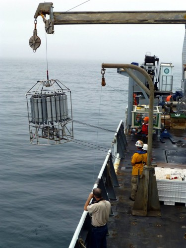 Researchers aboard the research vessel Thomas G. Thompson lower a collection device into the waters of Barkley Sound, British Columbia, to capture water from a low-oxygen zone.