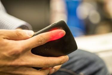 Photo of HemaApp illuminating a patient's finger
