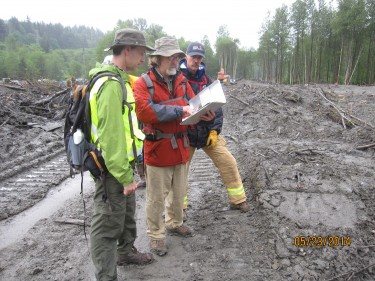 The new center builds on the UW team's post-disaster data collection expertise. Here, lead principal investigator Joe Wartman (left) reviews field notes following the 2014 Oso Landslide.