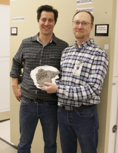 Two men posing with a fossil they discovered.