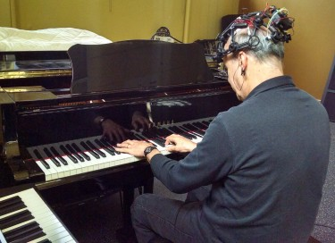 UW Music School Director Richard Karpen plays an electromagnetic piano called a Disklavier. Though he is shown performing on the keys, some of the music for the April 6 DXARTS Spring Concert will be played hands-free, with only the EEG.