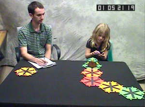 A 6-year-old girl follows instructions on a smartphone to program a robot turtle to follow a path of tiles.