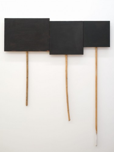 """3 Panel Glyph #2,"" oil on canvas on panel and sticks, by UW professor Denzil Hurley, courtesy of the artist and CANADA Gallery, New York. Part of an exhibit titled ""Disclosures"" at the Seattle Art Museum May 20 through November. The pieces depicted are black placard-like objects affixed to handle-like broomsticks."