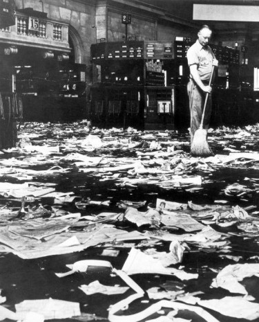 A cleaner sweeps the floor after the Wall Street crash of 1929.