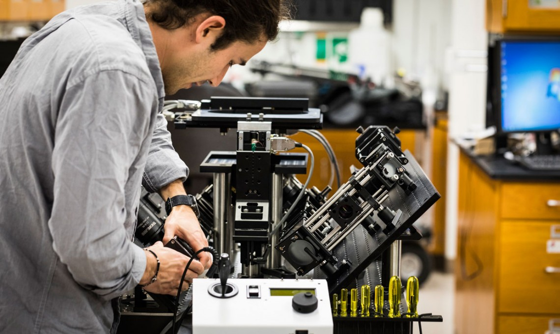 Photo of Adam Glaser tweaking microscope