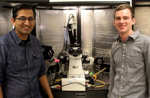 Two people standing next to a microscope.