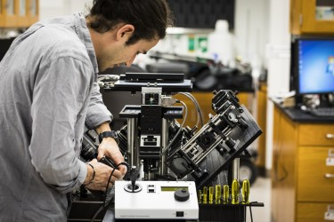 Photo of Adam Glaser tweaking microscope