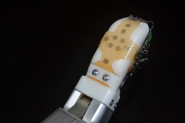 The bio-inspired sensor skin developed by University of Washington and UCLA engineers can be wrapped around a finger or any other part of a robot or prosthetic device to help convey a sense of touch.