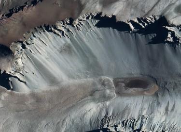 aerial image of dark spot in white valley