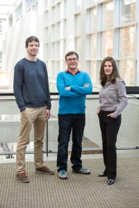 Three researchers standing in a lobby.