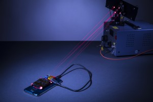 The wireless charging system created by University of Washington engineers. The charging laser and guard lasers are normally invisible to the human eye, but red beams have been inserted in place of the guard beams for demonstration purposes.