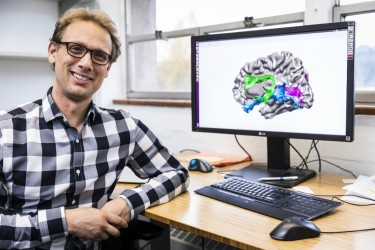 Jason Yeatman, an assistant professor in the UW Department of Speech and Hearing Sciences, shows an illustration of the brain in his office at I-LABS.