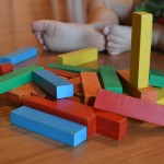 A University of Washington study finds that young toddlers conduct a form of cost-benefit analysis in deciding whether to help someone. Photo of blocks at an infant's feet.