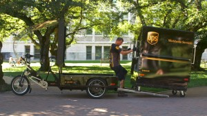 A UPS delivery person puts a cargo box on an e-bike