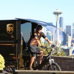 A UPS delivery person on an e-bike in front of the Space Needle