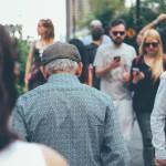 People walking in a crowd, looking at their phones.