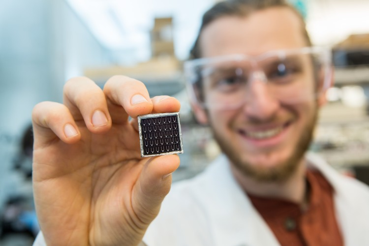 A person standing in a laboratory holding up a small solar cell