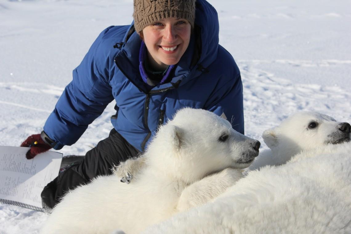 Laidre in blue parka with polar bear cubs