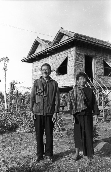 Becker's tour of the country was carefully managed by the Khmer Rouge, which wanted to show people content and at work in the countryside. Photo of couple outside a house.