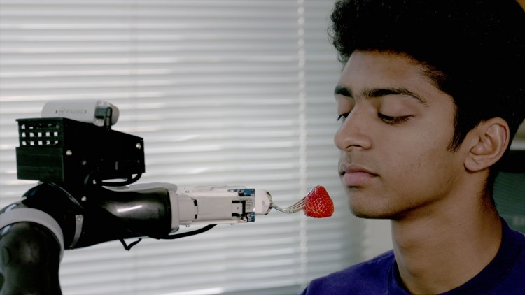A robot feeds a volunteer a strawberry