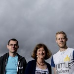 three people in front of gray sky