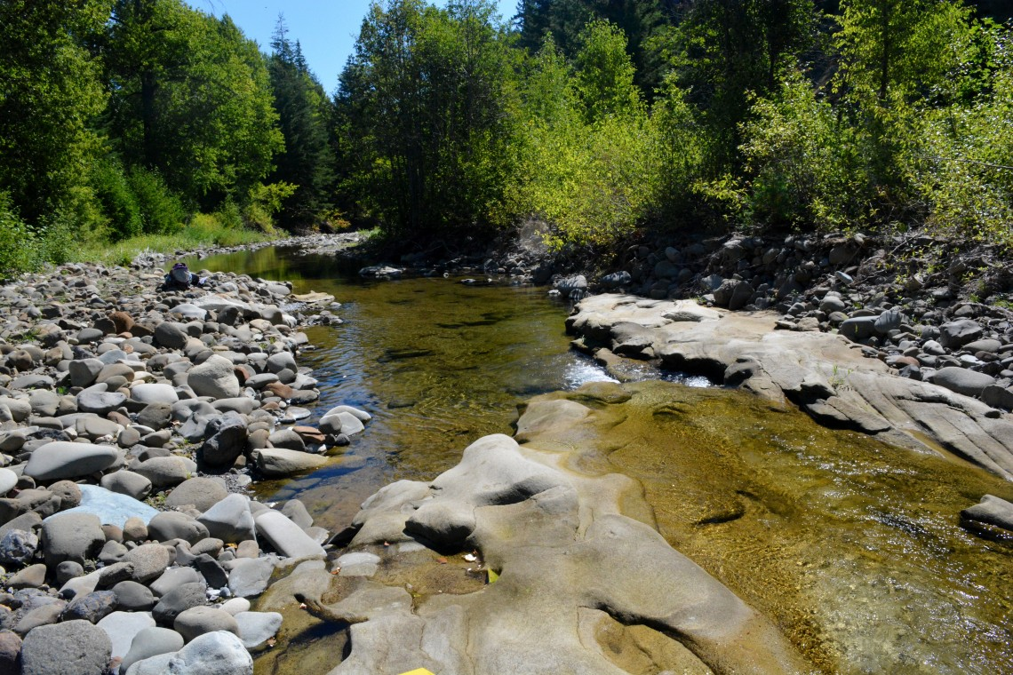 Exposed bedrock in the Teanaway River forms flutes and grooves — depressions where gravel gets trapped in a pothole and erodes it further. The oblong depressions are popular summer bathing spots.