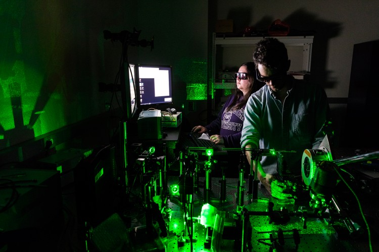 Two people operating a laser to heat material and make nanodiamonds.