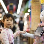 a small girl touches a robot's hand