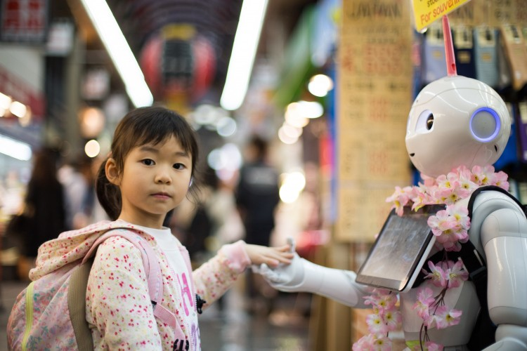 a girl touches a robot's hand