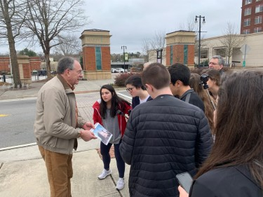 A Maryville resident explains to students the history of Preservation Plaza. Photo of older man talking to a group of teenagers outside.