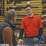 Man behind the counter of a gun shop talks to a customer.