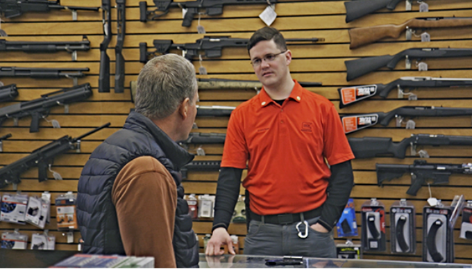 Man behind the counter of a gun shop talks to a customer.