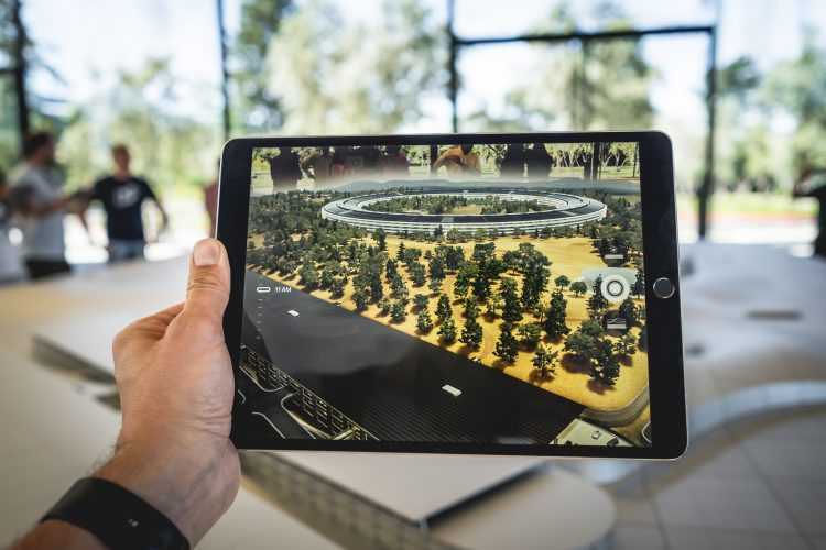 A person holding up an iPad that shows a digital world over the real world.