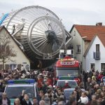 A large piece of scientific equipment being moved through a town