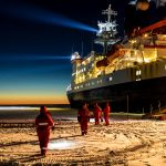 ship surrounded by sea ice and dark skies
