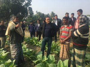 Faisal Hossain standing in a field with farmers around him