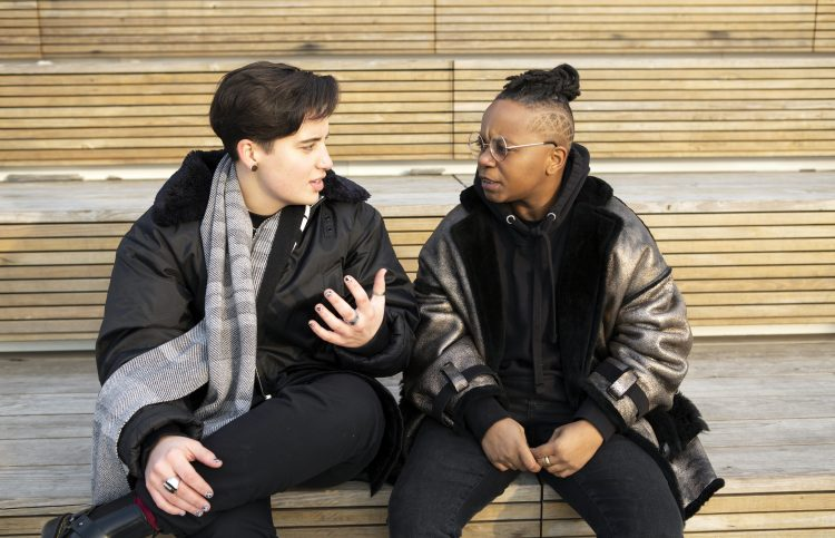 Two gender nonbinary people sit on steps outside and talk.