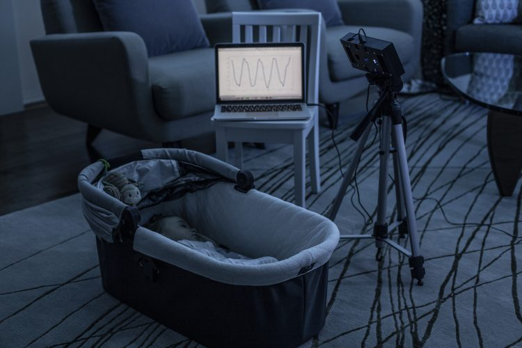 A baby is asleep while a smart speaker prototype monitors its breathing. The breathing waveform is shown on a computer screen nearby.