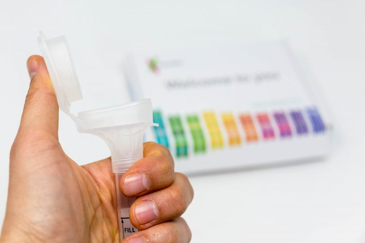 A hand holding a tube in front of a 23andMe kit