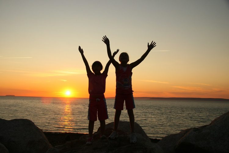 Photo of two children, in silhouette, on a beach